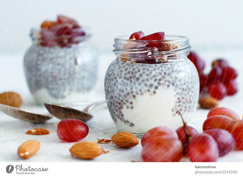 Chia pudding parfait with red grapes and almonds Yoghurt Fruit Dessert Eating Breakfast Diet Spoon Dark Gray White jar chia Bunch of grapes nuts Pudding seed