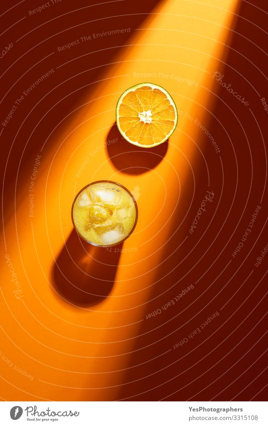 Glass of orange juice and sliced orange in sunlight. Fruit Orange Cold drink Lemonade Juice above view citrous Citrus fruits colorful cut in half flat lay