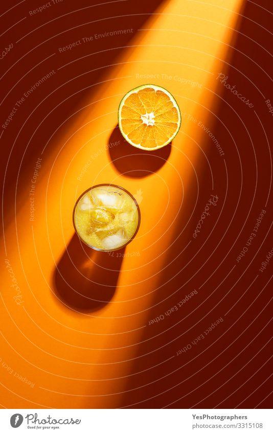 Glass of orange juice and sliced orange in sunlight. Fruit Orange Cold drink Lemonade Juice above view citrous Citrus fruits colorful cut in half flat lay