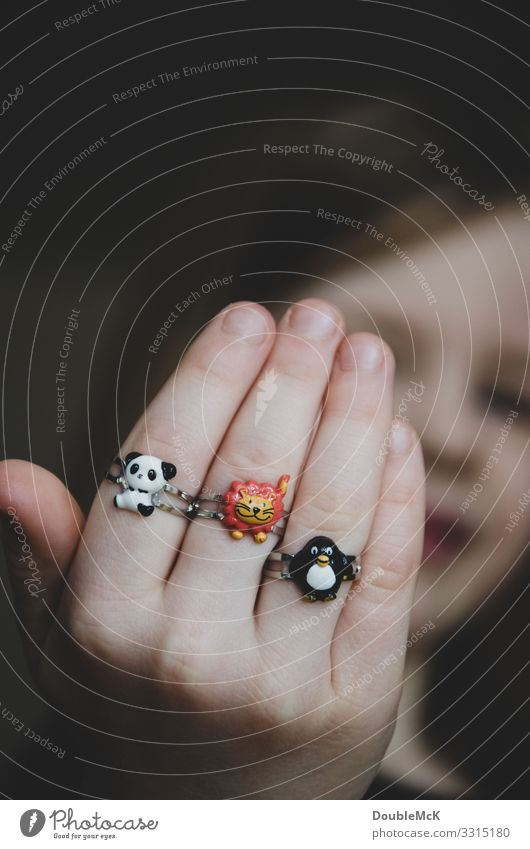Girl proudly shows her three rings on her fingers Human being Feminine Child girl Infancy Head by hand Fingers 1 3 - 8 years Ring Animal Panda low Penguin