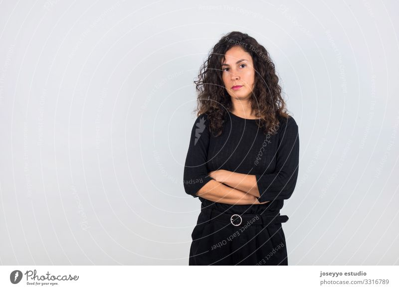 Brunette woman with black shirt and arms crossed. 30 - 45 years attitude Beauty Photography Brown Casual clothes Curly hair dressed in black Elegant empowerment