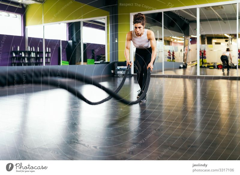 Young and athletic woman using training ropes in a gym. Lifestyle Personal hygiene Body Wellness Club Disco Sports Rope Human being Feminine Woman Adults