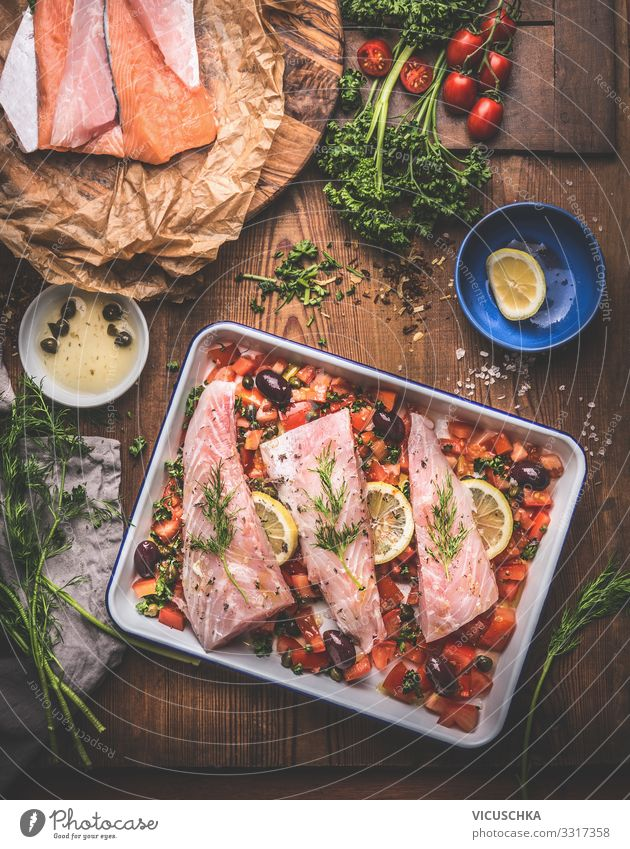 Cooking preparation of Bass fish fillets in Mediterranean sauce with tomatoes, olives and capers in baking pan on rustic wooden background with ingredients. Top view