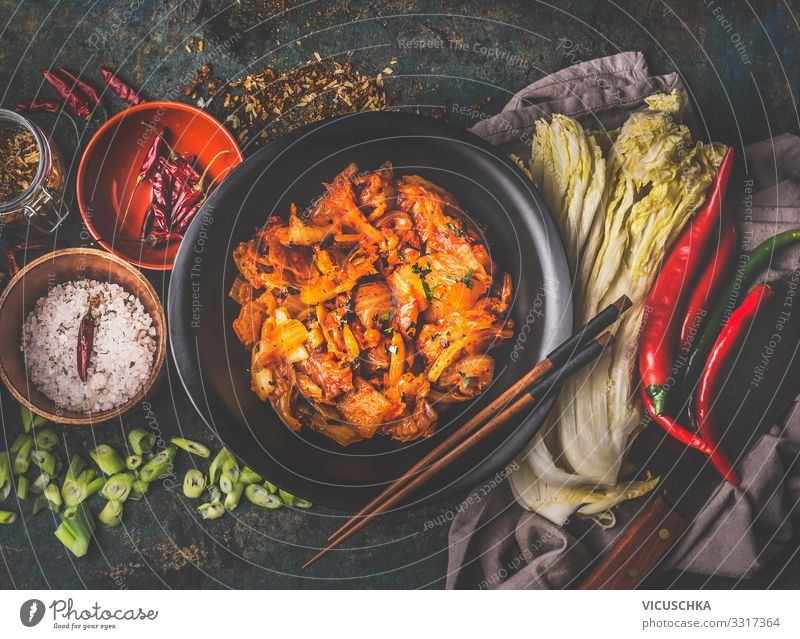 Homemade kimchi in black bowl on rustic background with ingredients: chinese cabbage , chili, spices and salt . Top view. Healthy fermented food homemade