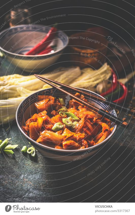 Kimchi, fermented chinese cabbage in hot chili sauce , in bowl with chopsticks on rustic kitchen table. Close up kimchi close up korean dishes korean style food