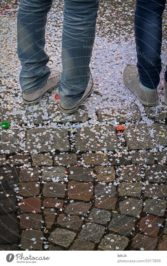 Three legs in jeans and sneakers, standing on the street in confetti, at carnival. Legs feet showery with confetti Confetti celebration celebrations Street