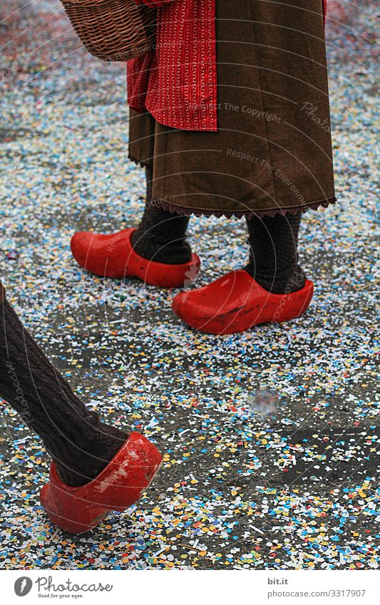 Three legs stand and walk in red Dutch clogs; clogs and apron dressed up in the street covered with confetti, on Mardi Gras during a carnival parade, the traditional Buernfasnachtin Südbaden.