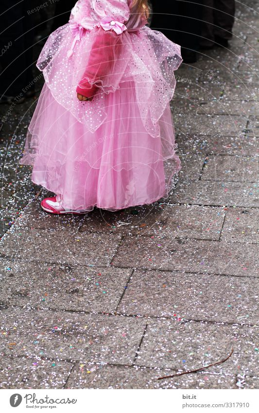 Little playful, dreamy, pretty, beautiful, sweet, dressed up princess in pink, pink dress with tulle, stands at carnival, carnival as a spectator, visitors at the carnival procession in the street, on confetti and looks, watches, enjoys the party.