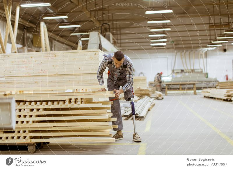 Disabled young man with artificial leg at the furniture factory Furniture Work and employment Profession Craftsperson Workplace Factory Industry Business Tool