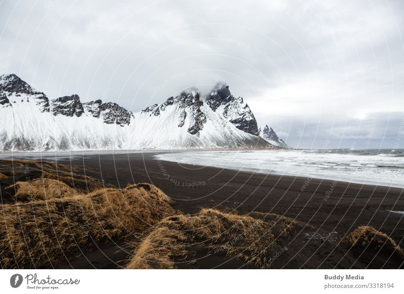 Stokksnes - Black Sand Beach in Iceland Vacation & Travel Expedition Mountain Nature Landscape Earth Water Sky Clouds Spring Weather Wind Grass Rock Waves Coast