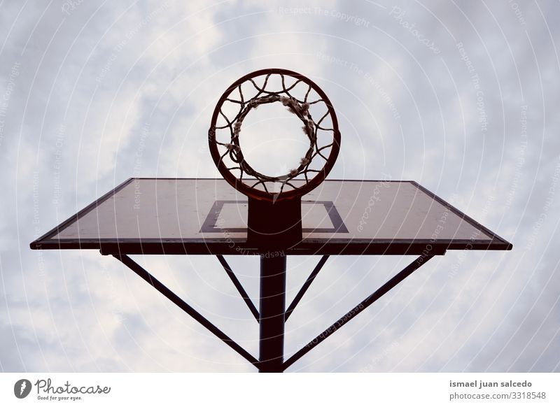 basketball hoop sports equipment on the street, street basket in Bilbao city Spain sky blue silhouette circle chain metallic net play playing playful old park