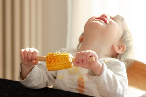 Ah, corn... Food Vegetable Maize Corn cob Eating Human being Feminine Child Toddler Girl 1 1 - 3 years To hold on Scream Cry Anger Yellow Pink White Emotions
