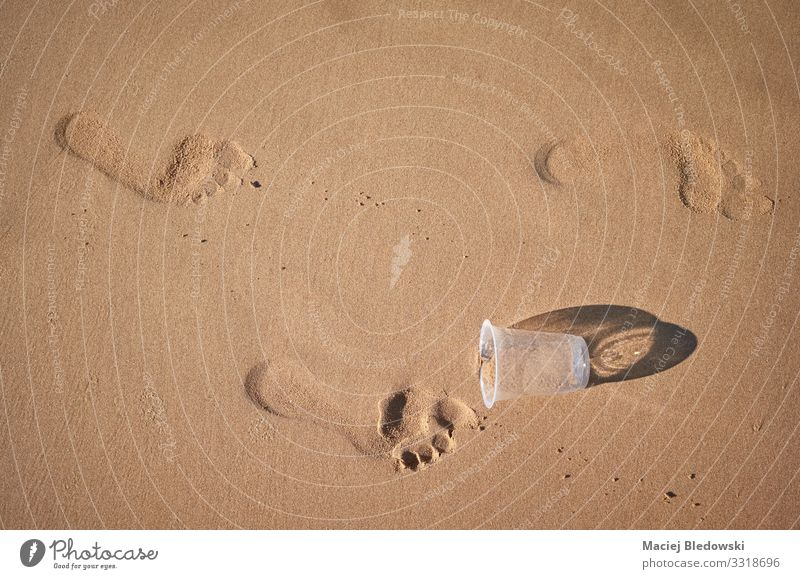 Footprints and plastic cup on a sandy beach. Lifestyle Vacation & Travel Tourism Summer vacation Beach Environment Nature Sand Plastic Environmental pollution