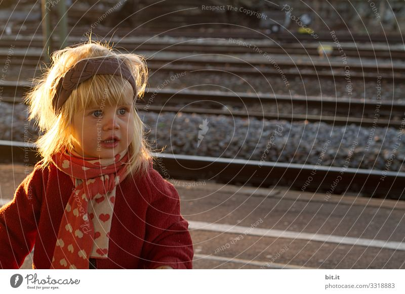 Blonde girl with big eyes, headband & scarf, stands in the autumnal soft evening light at the railway track and waits for visitors. Curious, cheerful child in warm clothes, waiting in the evening sunlight on the platform. Travel, travel by train, train.