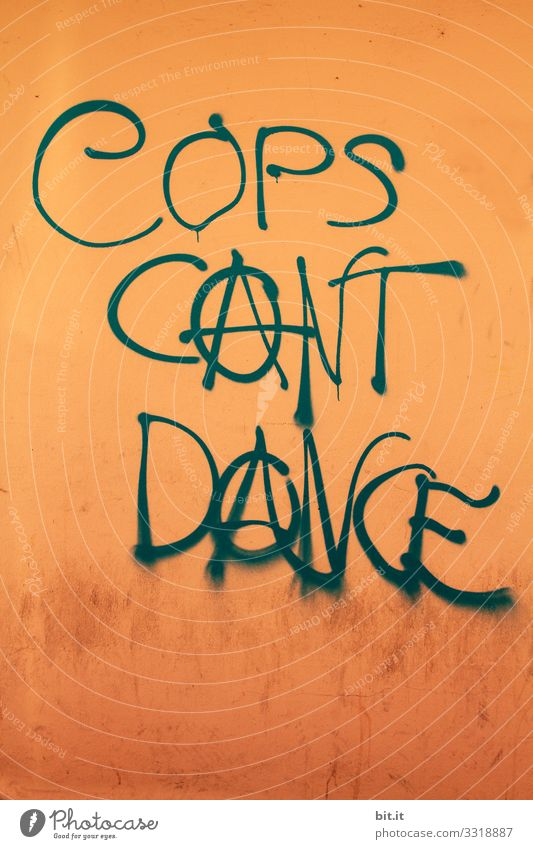 The police can't dance, it's written as writing on an orange wall. Ironic sign against police, for anarchy with anarchy cakes sprayed on wall. Symbol for anarchism, politics without power, leftists, freedom and left-wing movement.