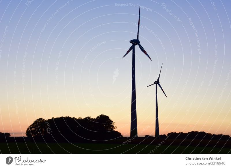 Two wind turbines at sunset / sunrise Wind energy plant Technology Advancement Future Climate Neutral Energy industry Renewable energy Cloudless sky Innovative