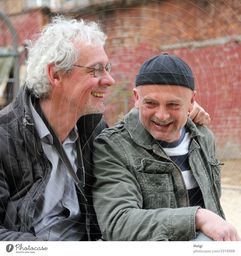 Portrait of two laughing seniors, one with silver-grey curls and glasses, the other with cap in front of an old wall Human being Masculine Man Adults