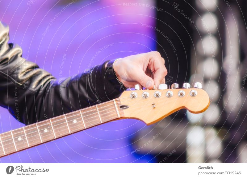 male hand musician tunes guitar close up Playing Music Man Adults Hand Fingers Concert Musician Guitar Rock Clothing Jacket Black Colour background