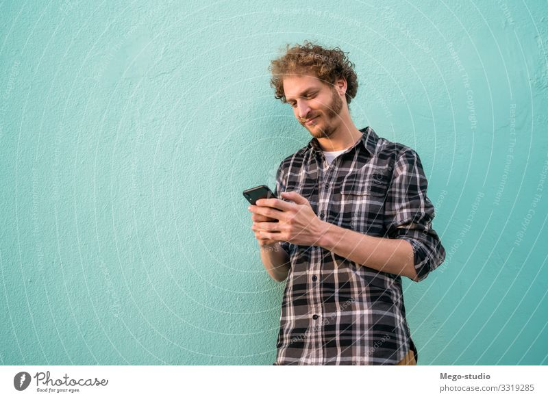 Portrait of young man using his mobile phone against blue background. Communication concept. Lifestyle Style Joy Happy Contentment Telephone PDA Technology