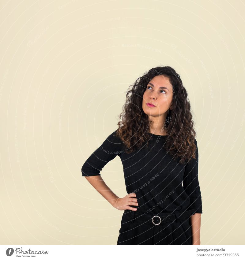 Brunette woman looking up with thoughtful gesture 30 - 45 years attitude Beauty Photography Brown Casual clothes Concentrate Curly hair dressed in black