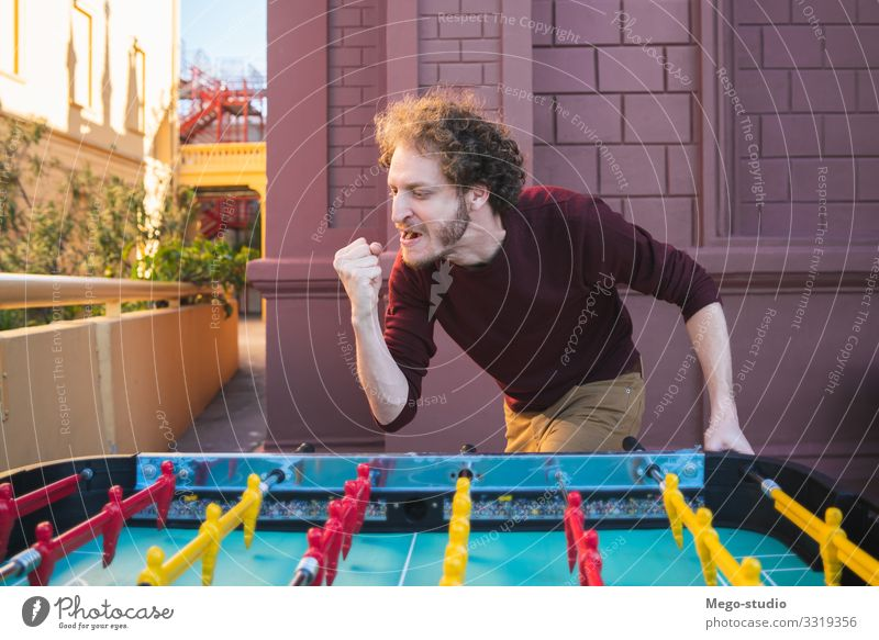 Young man playing table football. Lifestyle Joy Happy Face Relaxation Leisure and hobbies Playing Table Entertainment Sports Soccer Human being Man Adults Toys