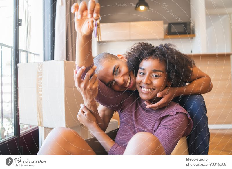 Latin couple having fun with cardboard boxes in new house. Woman Human being Youth (Young adults) Man Beautiful House (Residential Structure) Relaxation Joy