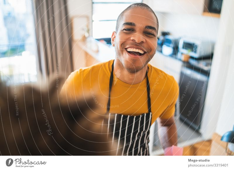 Young latin man dusting his new house. Man House (Residential Structure) Black Adults Work and employment Clean Good Furniture Home Household Hold Housekeeping