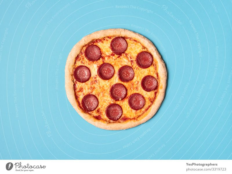 Pizza salami on a blue background. Whole pizza pepperoni. Food Dough Baked goods Nutrition Lunch Dinner Fast food Finger food Italian Food Delicious Blue Yellow