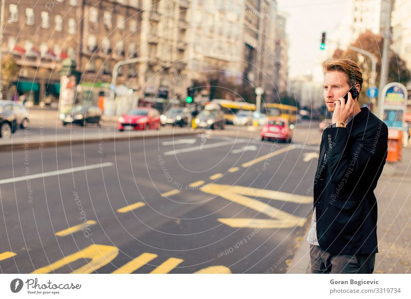 Young man on the street with mobile phone Lifestyle Telephone PDA Technology Human being Youth (Young adults) Man Adults Autumn Building Street Beard Stand