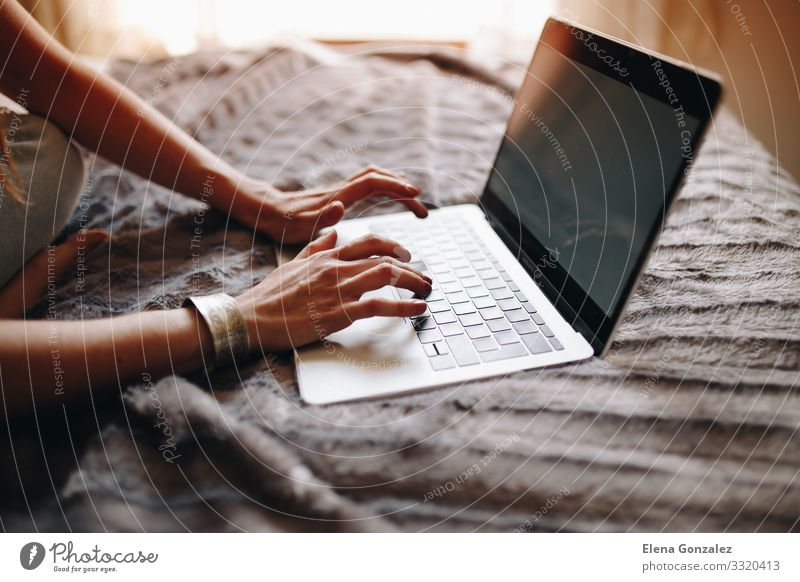 Woman's hands typing on laptop keyboard in the cozy bedroom. Lifestyle Academic studies Work and employment Profession Workplace Office Financial Industry