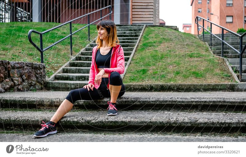 Female athlete posing sitting on the stairs outdoors Woman Human being Adults Natural Sports Grass Body Smiling Sit Action Fitness Posture Thin Top Sneakers