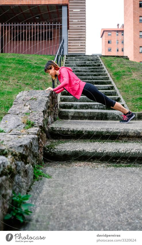 Female athlete doing push-ups outdoors Happy Body Sports Human being Woman Adults Grass Sneakers Fitness Thin Natural sportswoman supported wall stairs urban