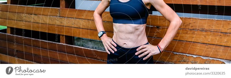 Cheerful female athlete in front of a wooden background Lifestyle Body Sports Internet Human being Woman Adults Brunette Fitness Stand Athletic Authentic Thin