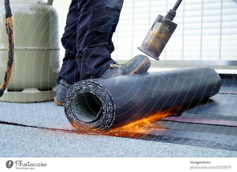 Flat roof installation with gas burner. Flat roof sealing. Flat roof installation with gas bottle propane blowtorch during construction with roofing felt. Heating and melting of bitumen tar paper. Roofer works. Roofer working tool. Waterproofing