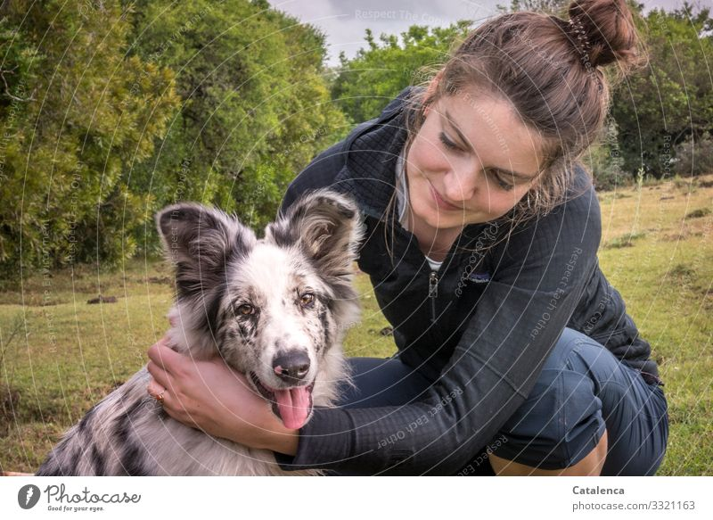 The young woman smilingly hugs her dog who looks into the camera with interest Human being feminine Young woman Animal Pet Dog youthful frisky panting luck