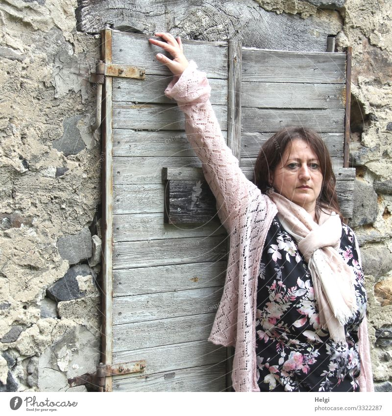 long-haired brunette woman with patterned dress, pink jacket and pink scarf is standing in front of a wall with old closed wooden window Human being Feminine