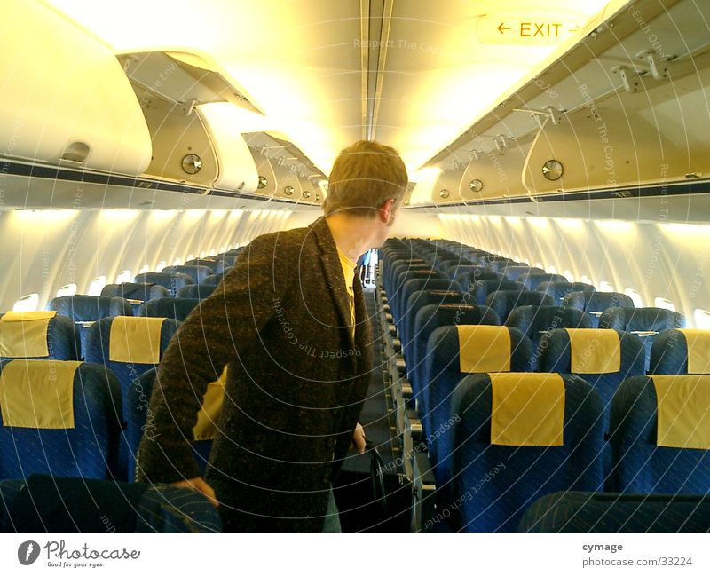 Human being Man Blue Vacation & Travel Yellow Airplane Masculine Aviation Row Coat Seating Row of seats Backwards Passenger Passenger plane