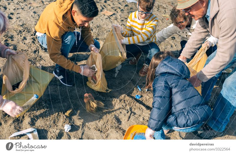 Volunteers cleaning the beach Woman Child Human being Nature Man Old Beach Adults Environment Family & Relations Boy (child) Group Together Dirty Smiling Trash