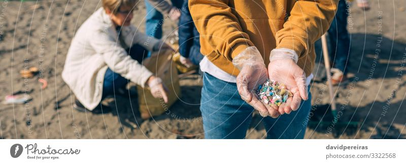 Hands with microplastics on the beach Human being Man Old Beach Adults Environment Group Sand Dangerous Internet Plastic Indicate Trash Teamwork Horizontal