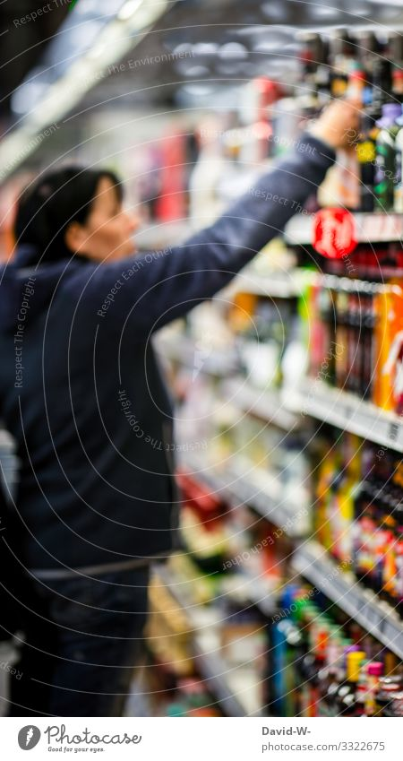 Woman looks at the goods on a supermarket shelf Shopping Trolley Food Supermarket Colour photo Consumption Store premises Human being consumer by hand