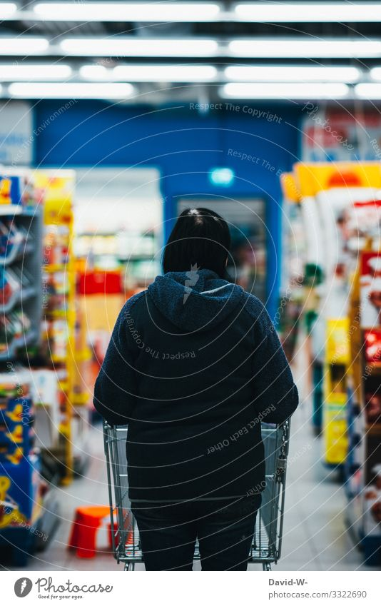 Woman walks through the store with the shopping cart Shopping Trolley Food Supermarket Colour photo Consumption Store premises Human being consumer by hand