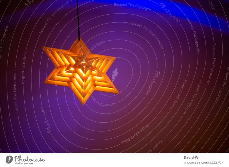 a shining star hangs from the ceiling against a blue illuminated background Illuminate luminescent Stars Christmas already wooden star Blue colourful