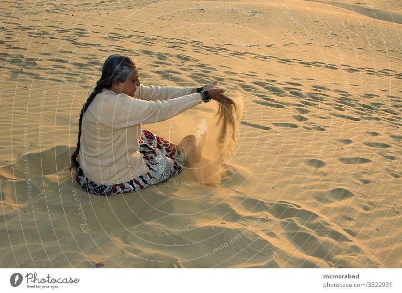 Playful Lady at Sand Dunes Joy Playing Vacation & Travel Woman Adults Places Drop To enjoy Yellow Gold Colour Horizontal Asia India Rajasthan Jaisalmer