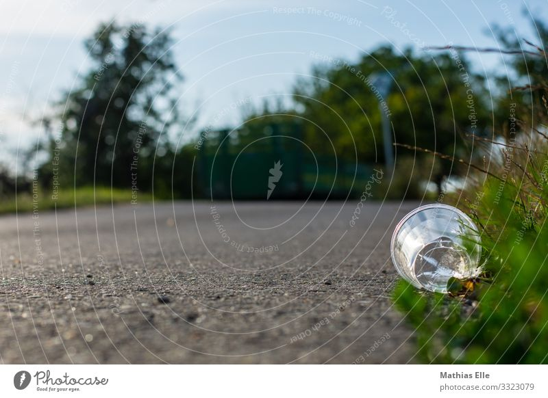 Plastic cups at the roadside Cup Mug Glass Environment Nature Landscape Grass Bushes Street Concrete Blue Gray Green Silver Environmental pollution