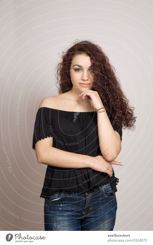 thoughtful young woman with long curly hair Human being Feminine Young woman Youth (Young adults) Woman Adults 1 13 - 18 years 18 - 30 years Jeans Blouse