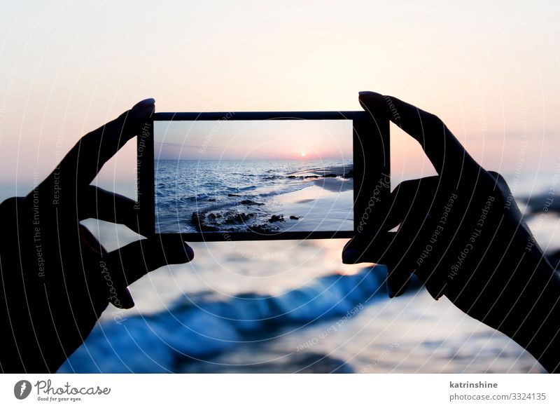 Girl is taking a sunset photo on the mobile phone Vacation & Travel Summer Beach Ocean Cellphone PDA Technology Woman Adults Hand Environment Nature Landscape