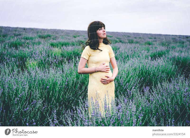 Lovely young woman in her first month of pregnancy pregnant brunette lavender flowers spring weeks one month two beggining floral field nature natural real