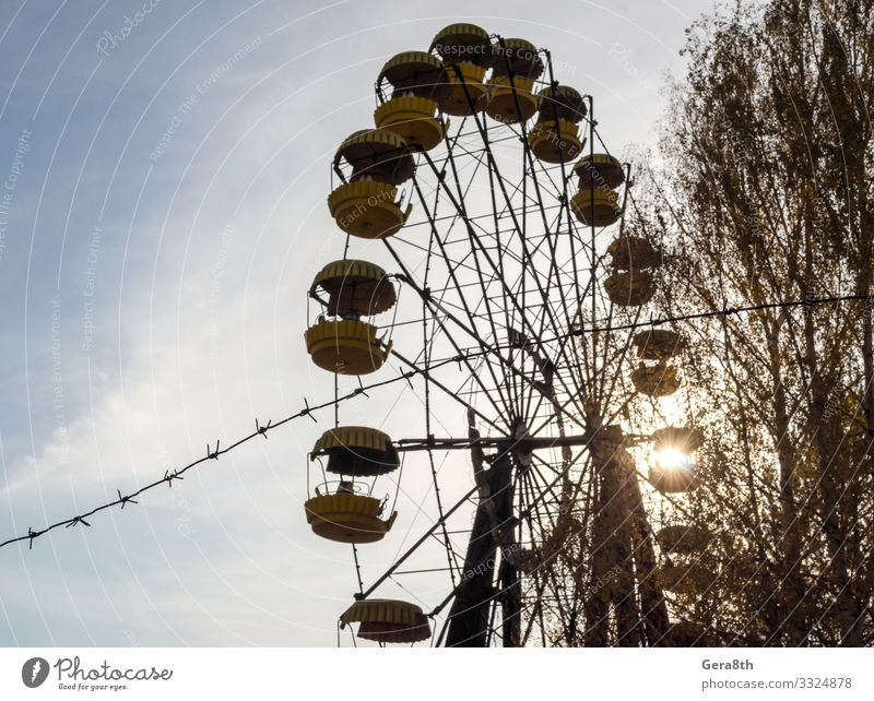 barbed wire and cabins carousel wheel in Chernobyl Vacation & Travel Tourism Trip Plant Sky Autumn Tree Park Metal Old Threat Blue Yellow Dangerous Disaster