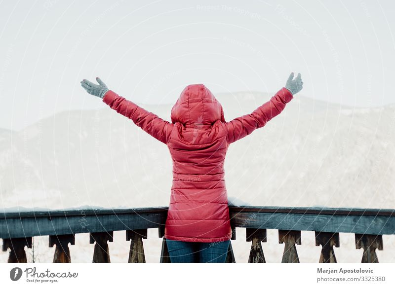 Woman standing with her hands raised facing the mountains Lifestyle Vacation & Travel Tourism Trip Adventure Freedom Winter Winter vacation Mountain Feminine