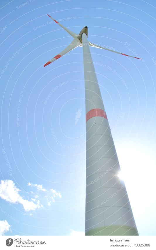 Wind turbine against a blue sky with sun and clouds, Rhineland-Palatinate, Germany. alternative energy, new natural landscape Wind energy plant Blue sky Clouds